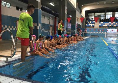 alumnos en el borde de la piscina